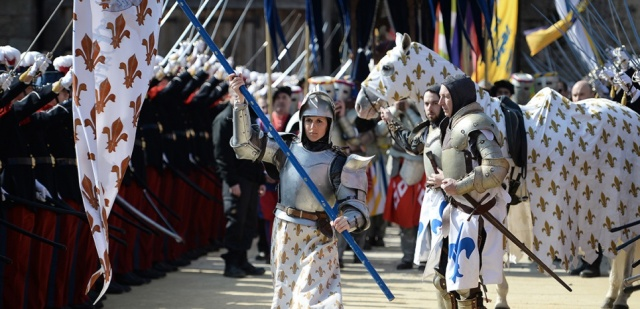 "An actress in the role of Joan of Arc performs during a ceremony as part of a presentation of a 15th century ring believed to have been owned by the French heroine on March 20, 2016 at the Puy du Fou historical theme park in Les Epesses, western France. The Puy du Fou foundation announced in early March 2016 to have bought the ring attributed to Joan of Arc and valued at 376,883 euros in Great Britain, but whose ""authenticity could not be certified"" by the L'Historial Jeanne d'Arc museum in Rouen. / AFP / JEAN-SEBASTIEN EVRARD"
